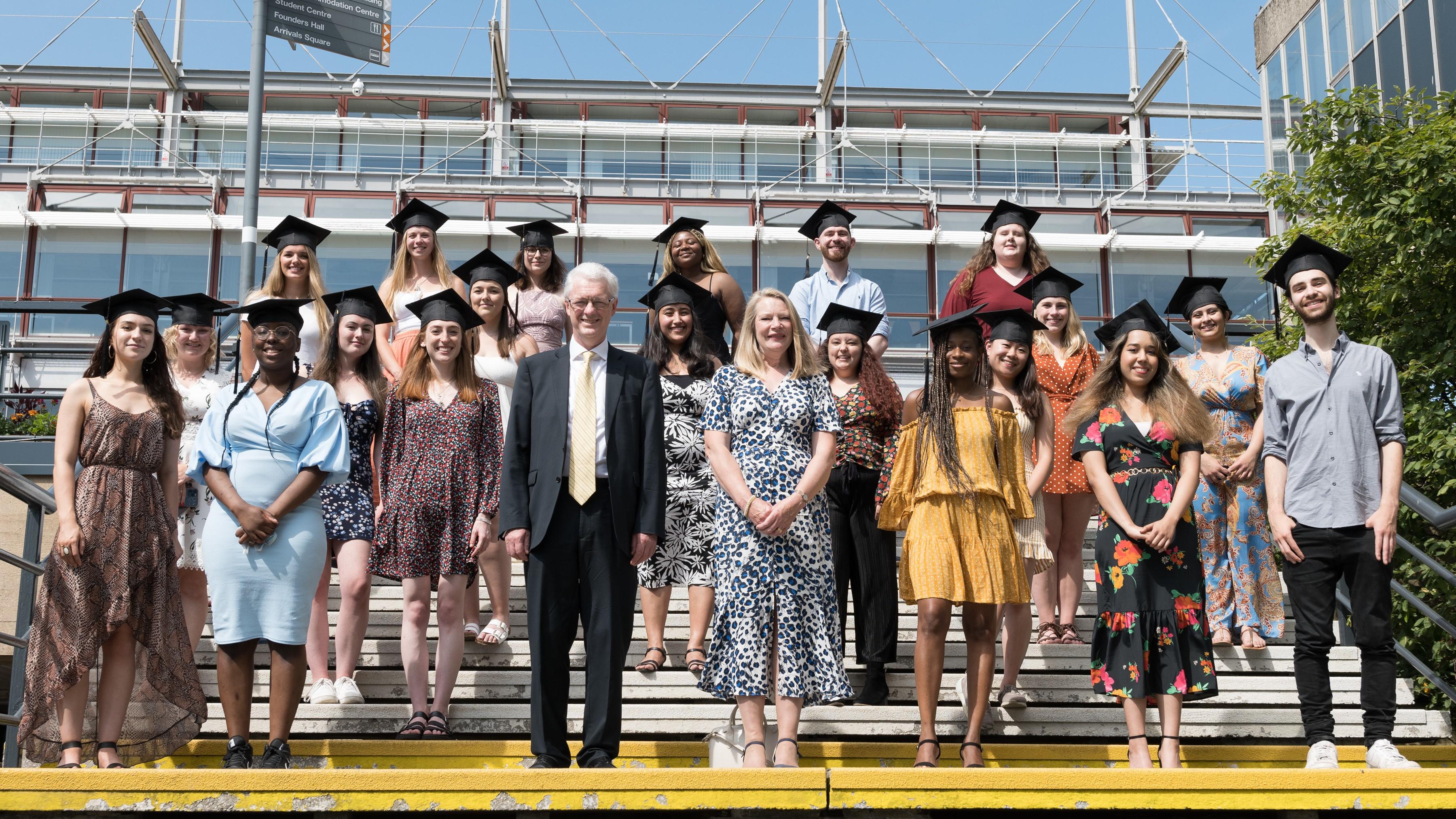 一群即将毕业的黄金奖学金获得者与伊恩·怀特和玛格丽特·怀特一起站在图书馆前的台阶上
