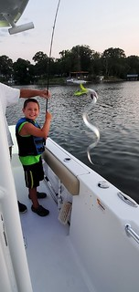 Photo of a boy on a boat holding a snake-like fish caught on his fishing rod