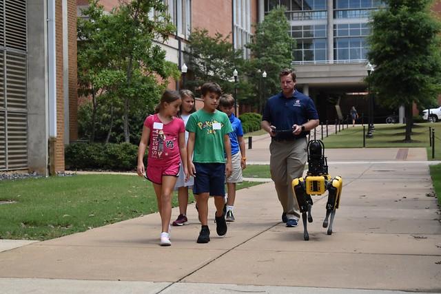Eric Wetzel and Mac walk with some robotics camp participants.