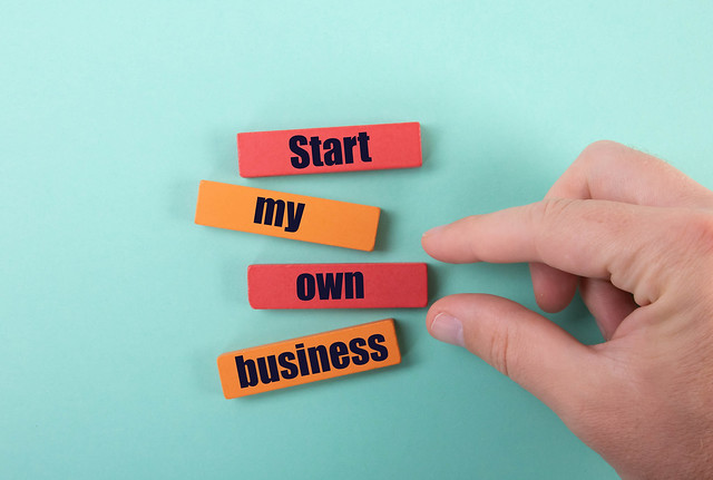 Hand and wooden blocks with Start my own business text