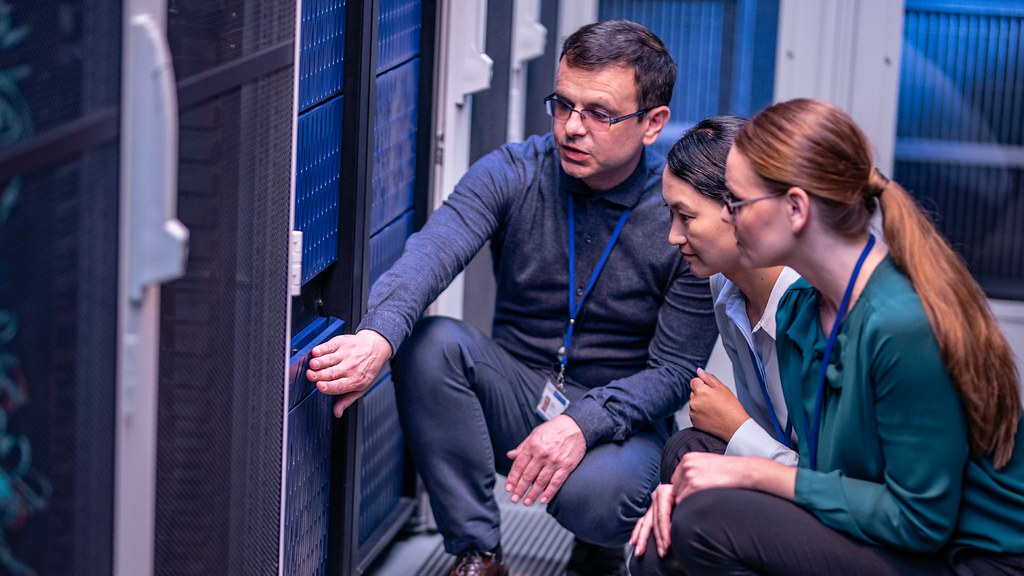 Software engineer explaining server configurations to two academic researchers.