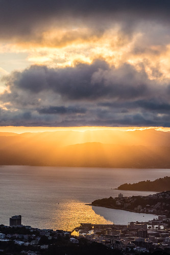 <p>Looking towards the rising sun lighting up Wellington's Overseas Terminal from behind heavy cloud.</p>