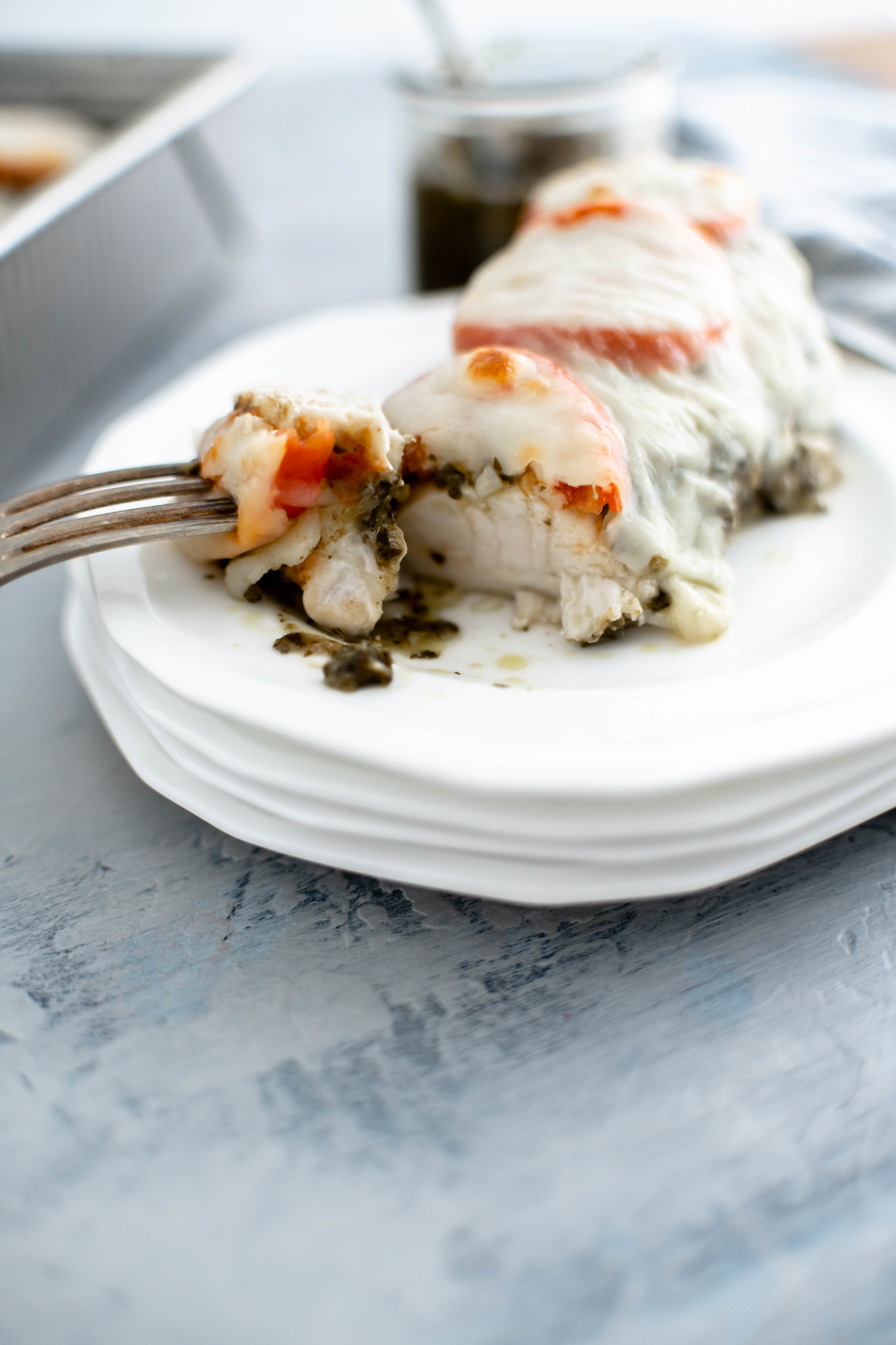 One pesto baked chicken breast on a white round plate with piece cut off on fork.