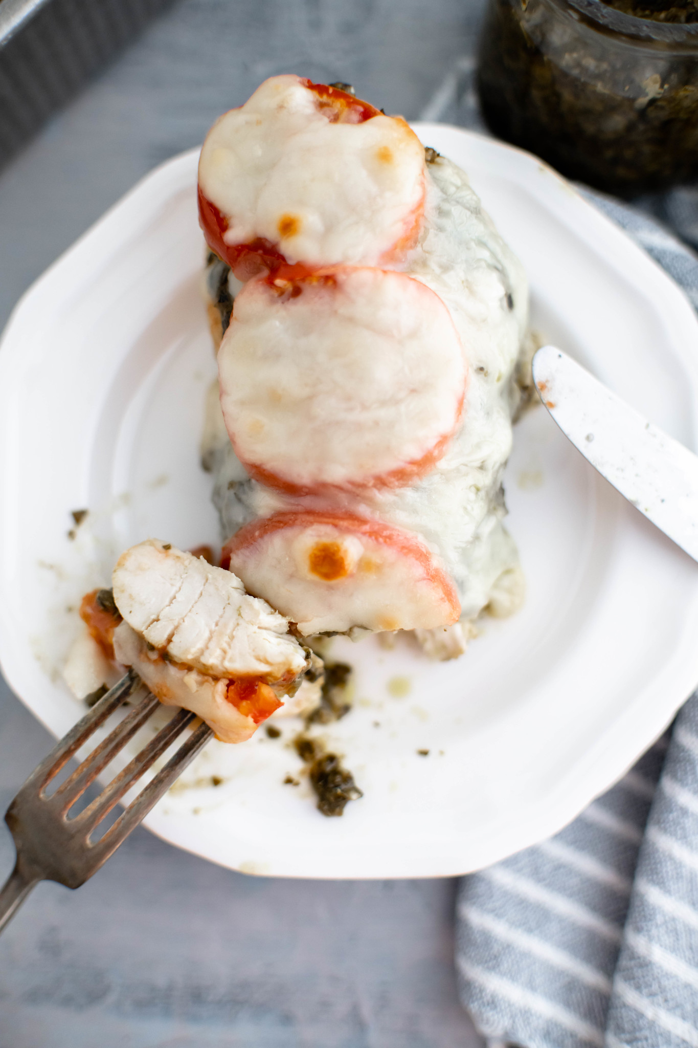Pesto baked chicken on plate with piece cut off on fork and facing up to show interior.