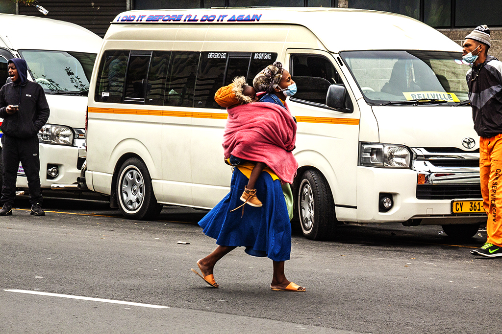 Woman with child on back crossing Strand on 9-3-21-- Cape Town
