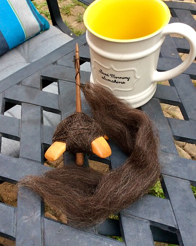 """Jenkins Delight spindle in Carob wood has a cop of Zwartables handspun wool yarn and the working fibre is laid to the front on a cast aluminum black faux lattice table.  A white coffee mug with yellow interior has cursive words on the front that read """"Good Morning Sunshine."""""""