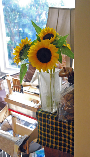 A square crystal vase with sunflowers is on a mercerized cotton table runner handwoven by irieknit in black, green, gold as an 8-shaft crepe weave.  A Louet Erica table loom on stand is in front of the bookcase with the runner.