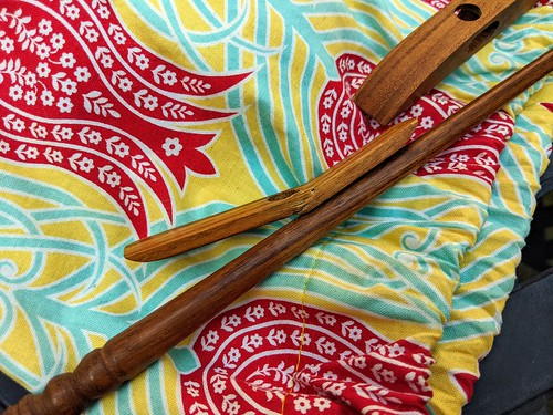 A spindle cross-arm from a butternut wood Ray's Turkish spindle is broken near the shaft hole of the flat arm.  It rests on a cotton cloth bag printed with a large stylized red tulip motif with white flower accents on a bright yellow ground with green stems and leaves outlined in white.  The intact shaft and second arm are below and above the broken piece respectively.