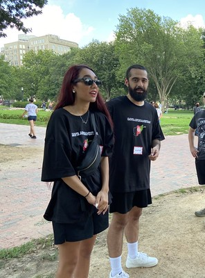 A woman and a man, both wearing black t-shirts bearing the Afghan flag, stand in a park.