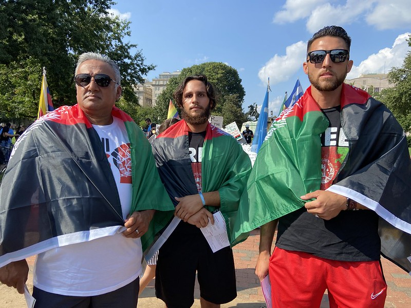 Three men stand together, each with an Afghanistan flag draped around their shoulders.