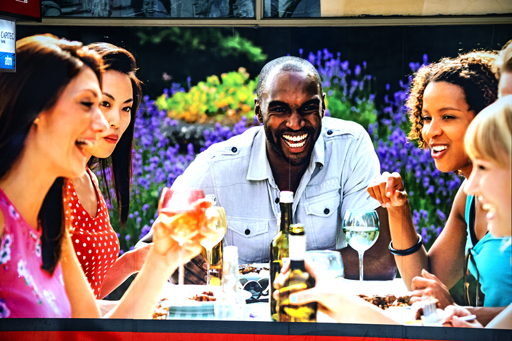 Laughing black man at a table with a colored, an Oriental and two white women--Cape Town