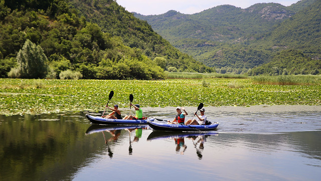 Paddling on River Crnojević through hills on both sides past colorful water lilies and puddles