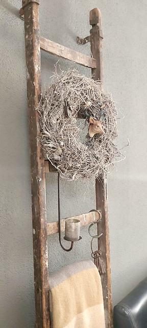 Houten decoratieladder met krans van takken en hangkandelaar