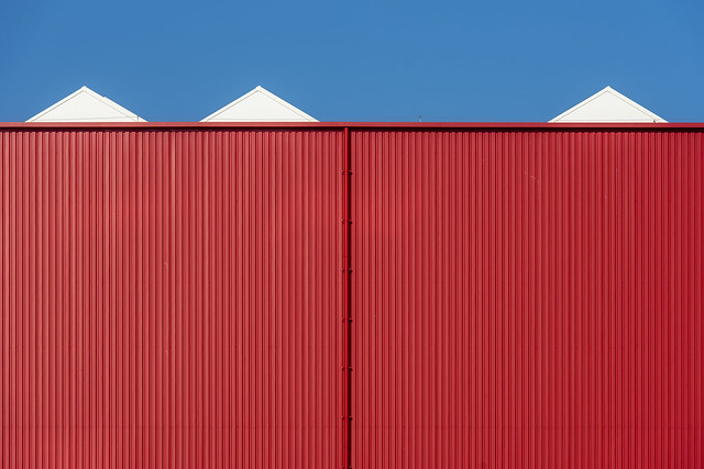 Red building with three white triangles (on Explore)