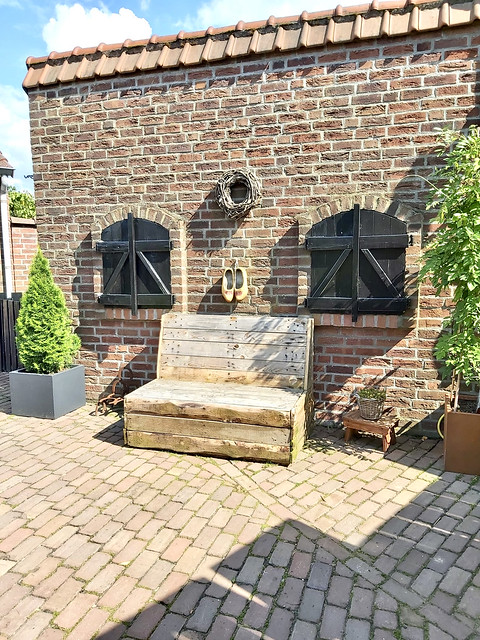 Houten tuinbank terras ramen met luiken boerderijwoning ommuurd terras