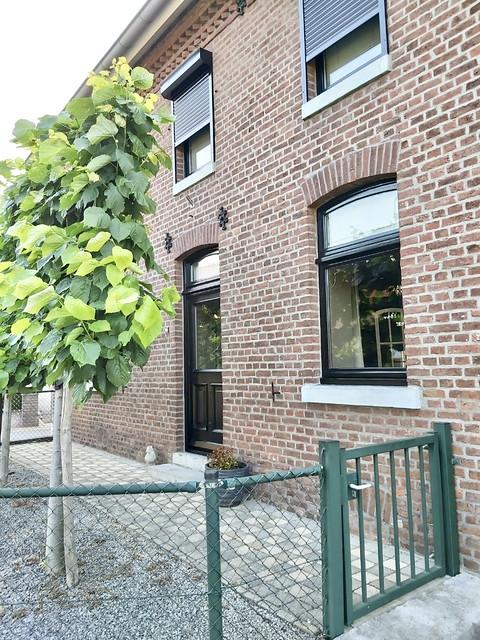 Voorgevel Limburgse boerderijwoning met zwarte kozijnen en voordeur