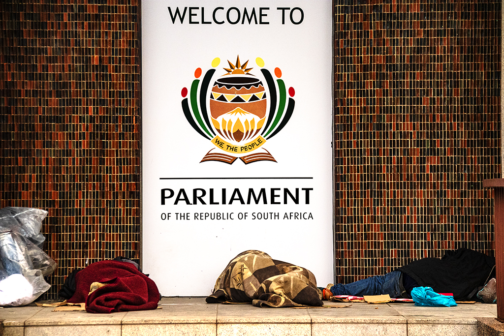 Homeless sleeping in front of WELCOME TO PARLIAMENT sign on 9-5-21--Cape Town