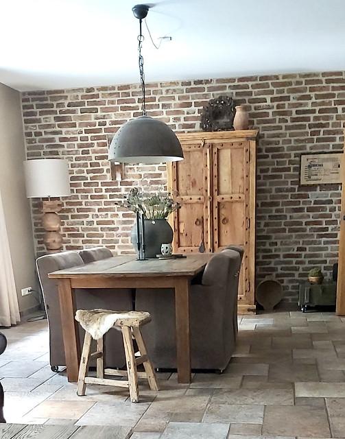 Landelijk sobere woonkamer schoonmetselwerk zadelkruk met vachtje kruik met takken