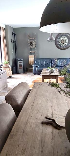 Landelijke sobere woonkamer leren bank decoratieladder krans houtkachel hoek