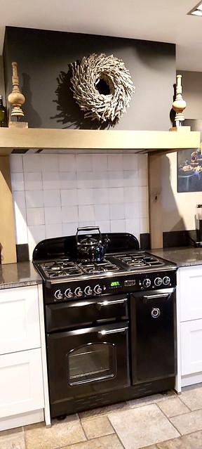 Lichte landelijke keuken met houten balk schouw