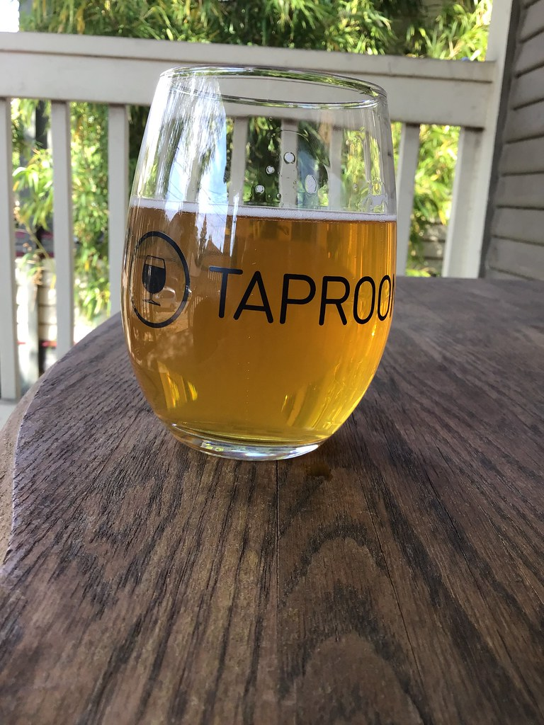Grains of Wrath's Overkill IPA in glass outside on table.