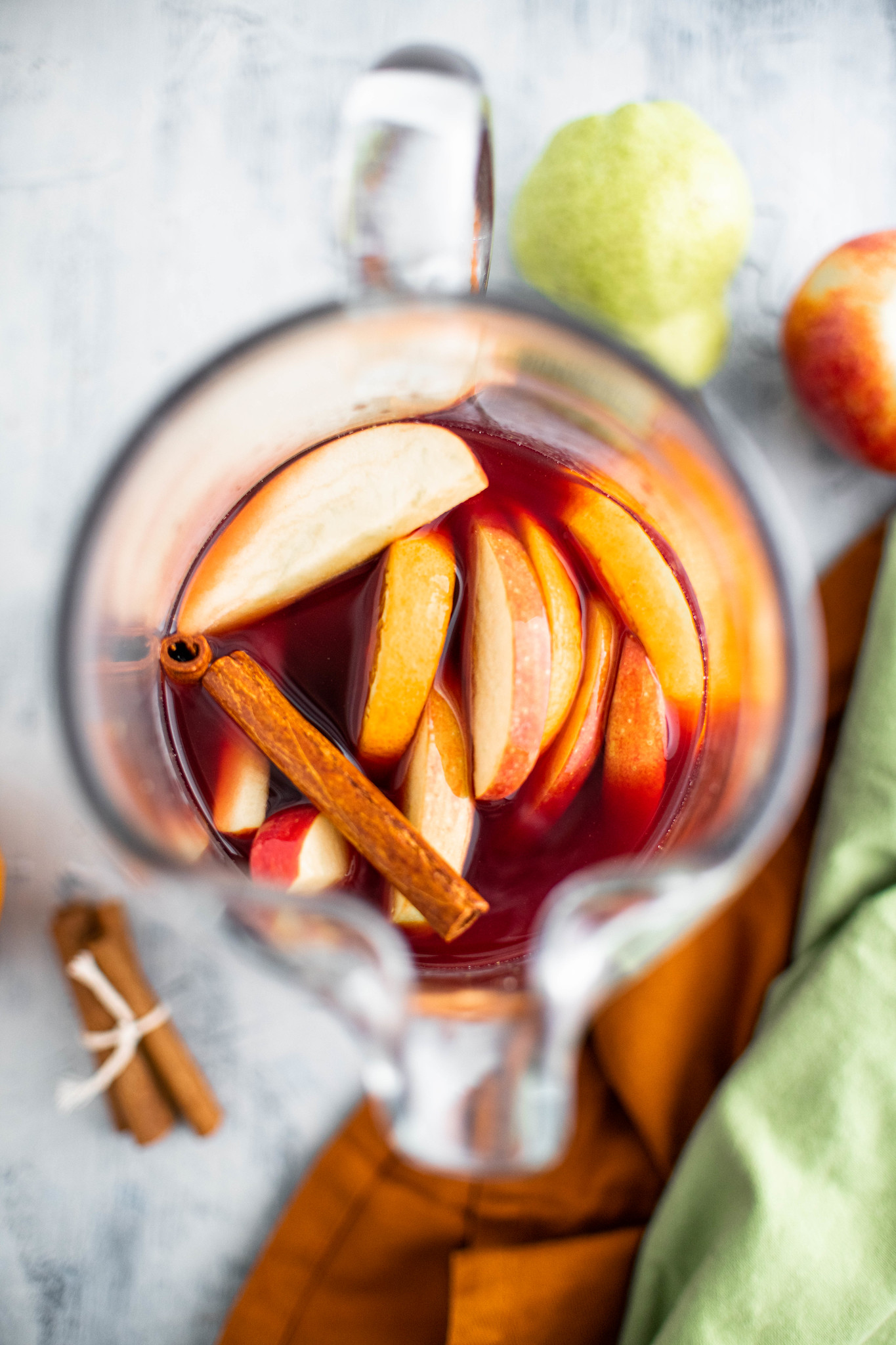 Photo straight down into pitcher of fall sangria with apple, orange and pear slices and cinnamon sticks.