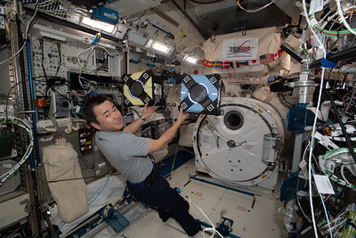 Astronaut Akihiko Hoshide checks out Astrobee robotic free-flyers