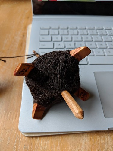 A Jenkins Lark cross-arm Turkish-style spindle in Tulipwood rests on a laptop with the underside winding of Zwartables wool shown.