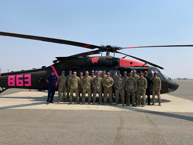 Wisconsin Army National Guard UH-60 Black Hawk crews from the Madison, Wis.-based 1st Battalion, 147th Aviation stand with their helicopter at Placerville Airport, Calif., September 1, 2021 where they are assisting in wildfire fighting operations.