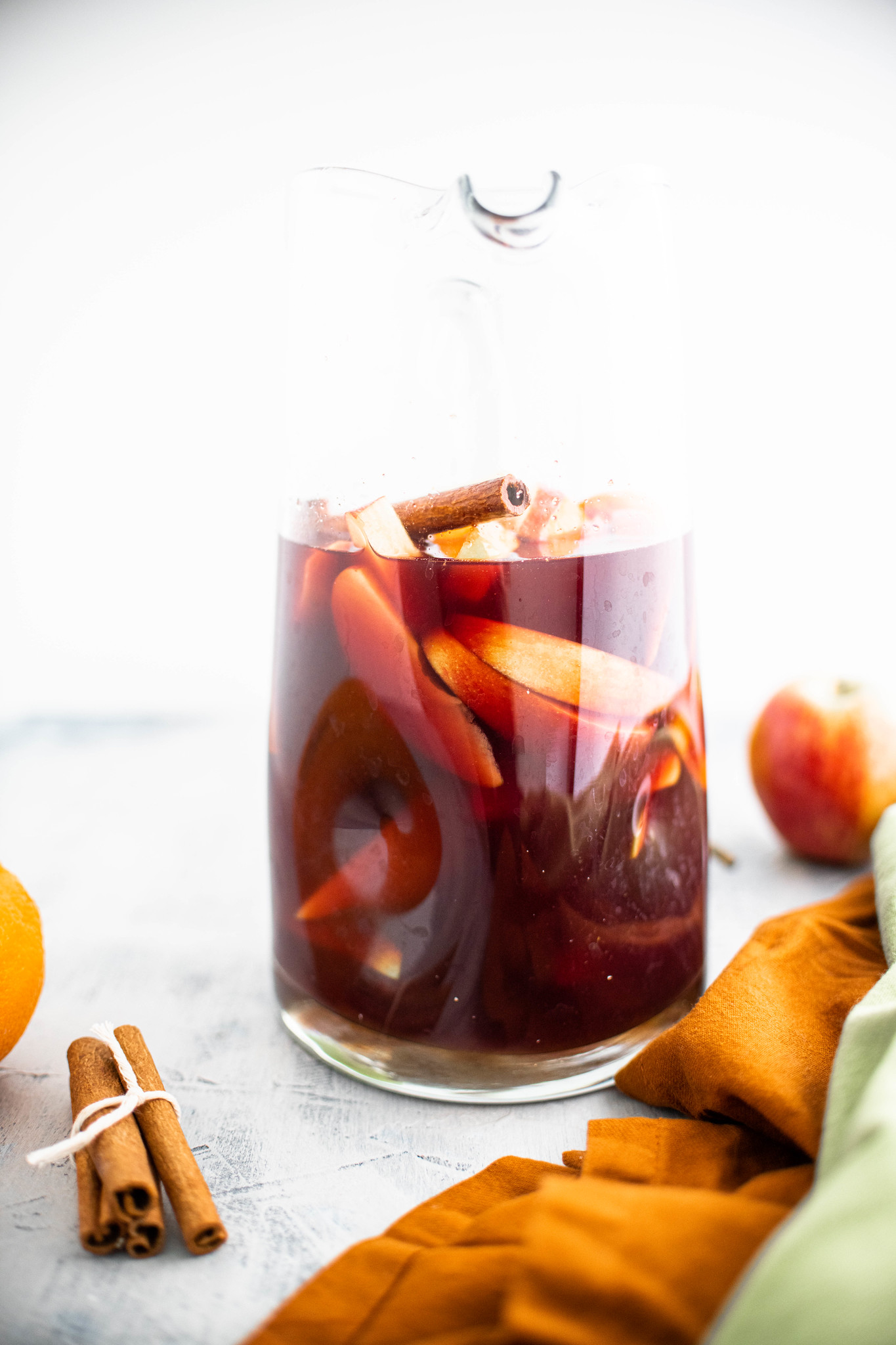 Straight on shot of pitcher of fall red sangria with cinnamon stick, apples, oranges and pears. Bundle of cinnamon sticks in upper left corner.