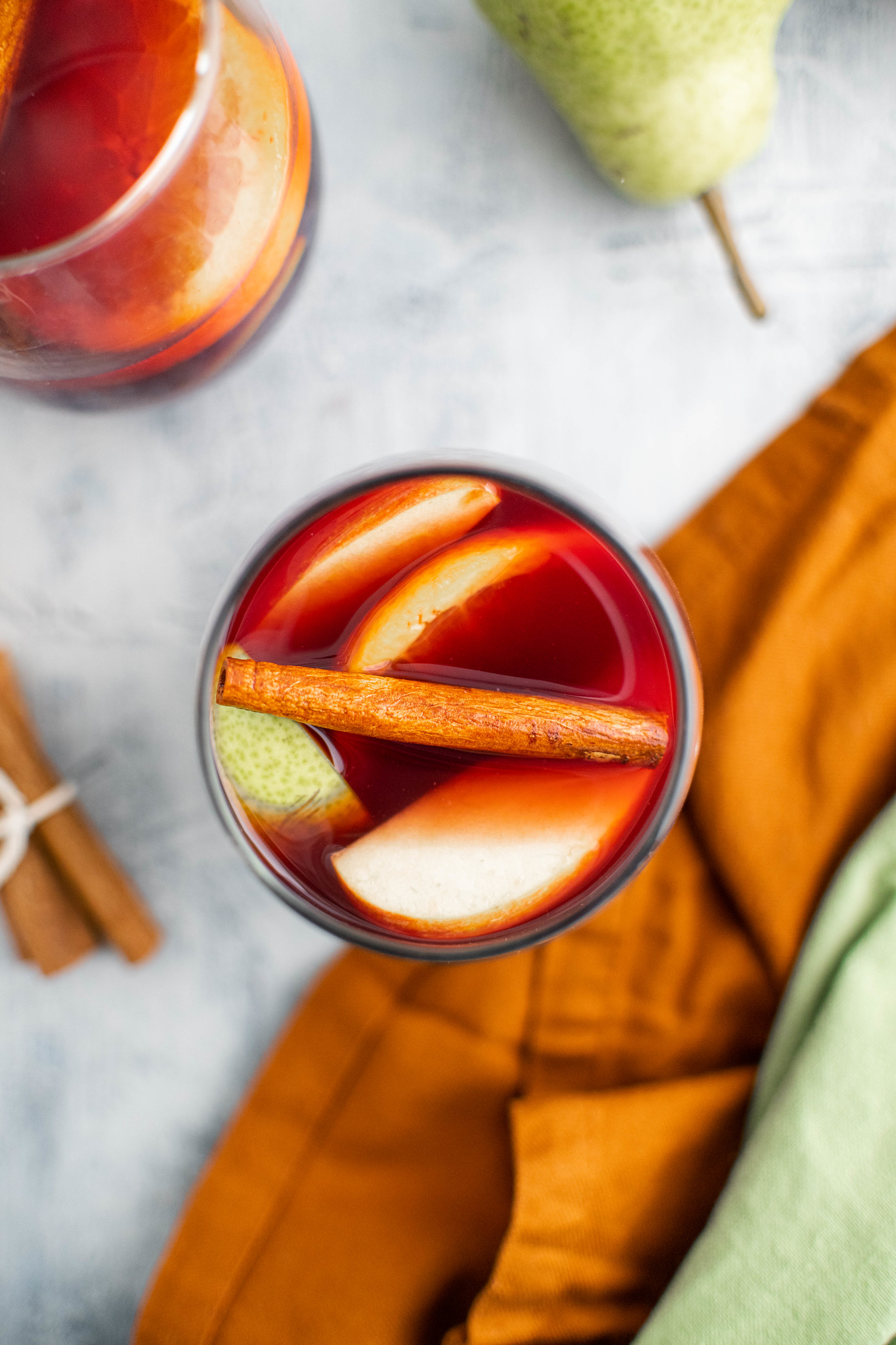 One glass of fall sangria in middle of photo with apples, pears, oranges and a cinnamon stick.