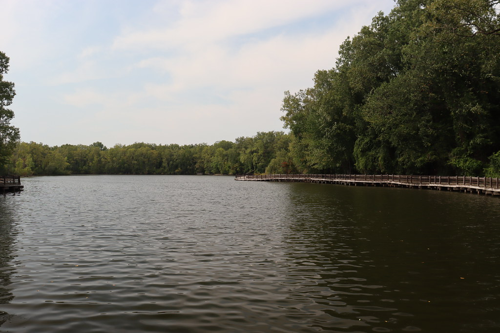 A photograph of the lake and trees and boardwalk at Hawk Island Park in Lansing, Michigan.