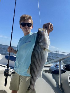 Photo of man in a boat holding a mid-sized striped bass
