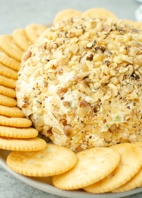 Cheese ball coated in walnuts on a white plate with Ritz crackers around it