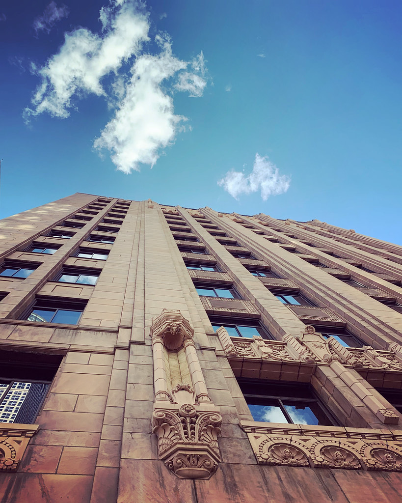 Looking up downtown to see blue sky and puffy white clouds above a 100+ year-old building