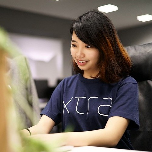 East Asian female student side on staring at a laptop