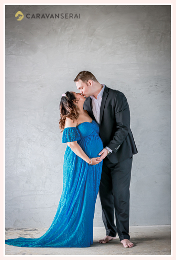 kissing couple in maternity photography, blue dress