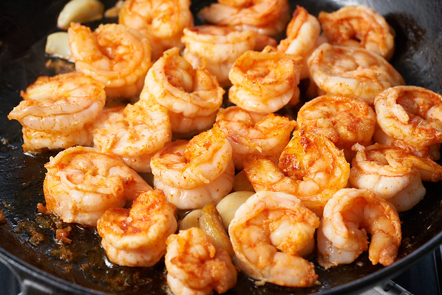 Keto meal fried shrimp for ketogenic diet, preparing sauce for pasta, seafood prawn sizzling in pan