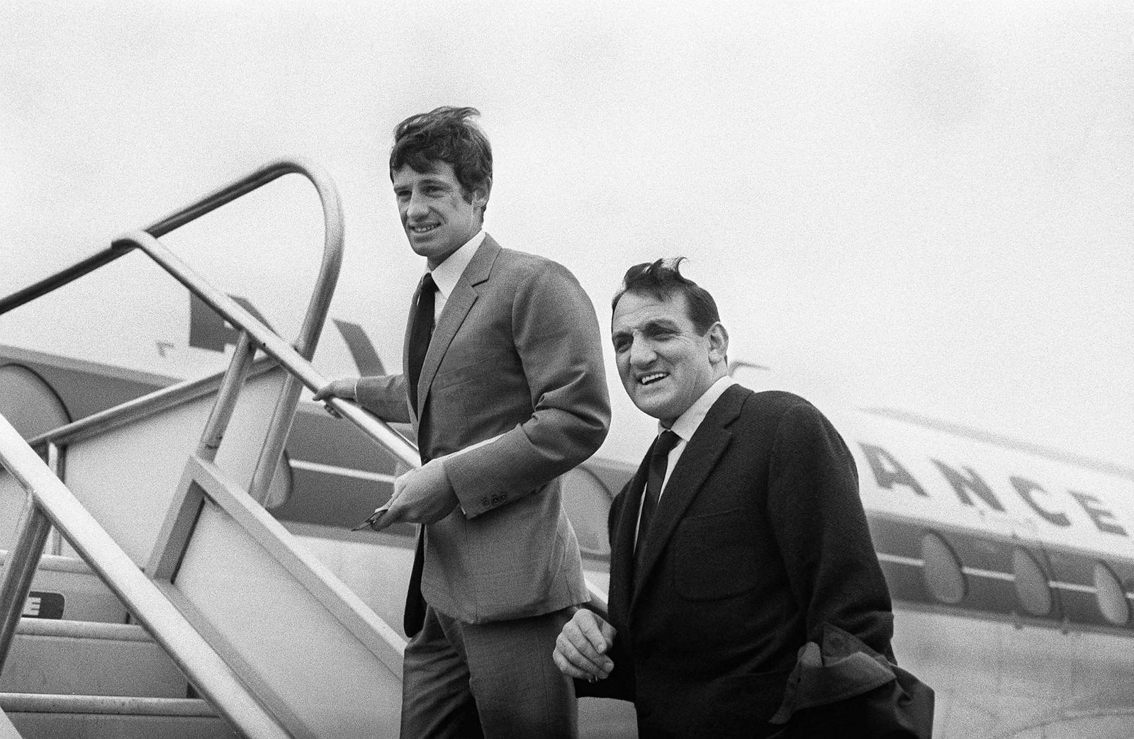 1963. Лино Вентура (справа) и Жан-Поль Бельмондо (слева) готовятся сесть на самолет, который доставит их в Касабланку, где будет сниматься фильм «100 000 долларов на солнце»