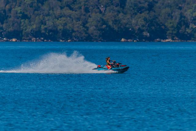 Girl riding a jet ski on the blue bay