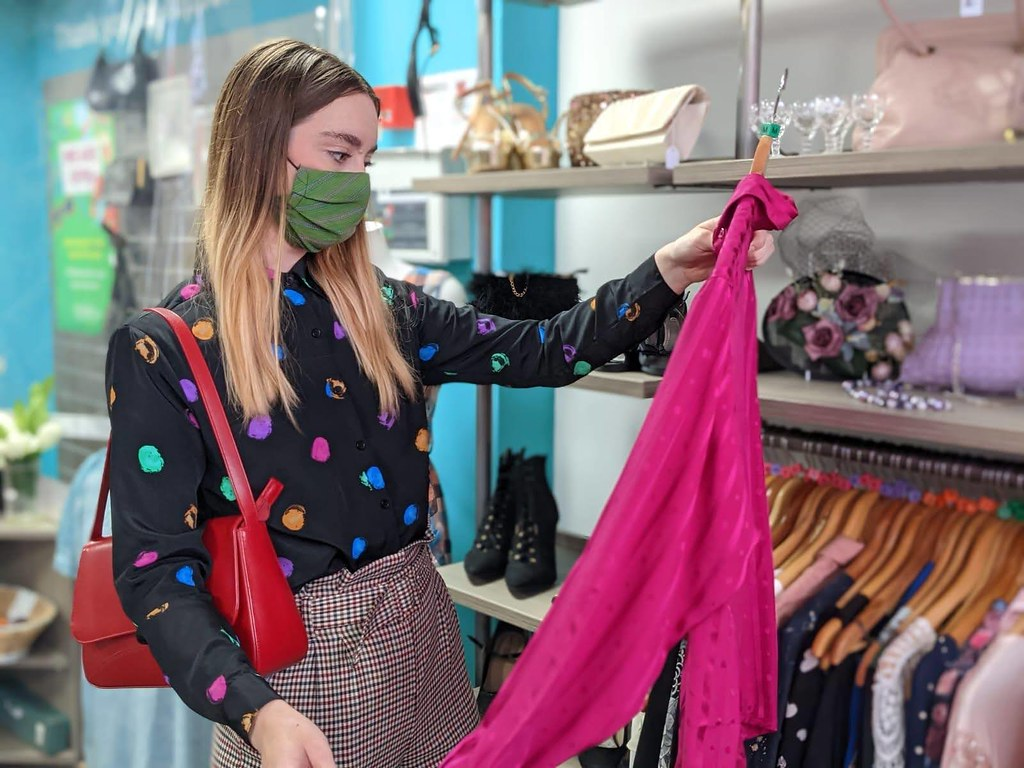 Chelsea Jade shopping in an Isabel Hospice charity shop, looking at a pink silk shirt.