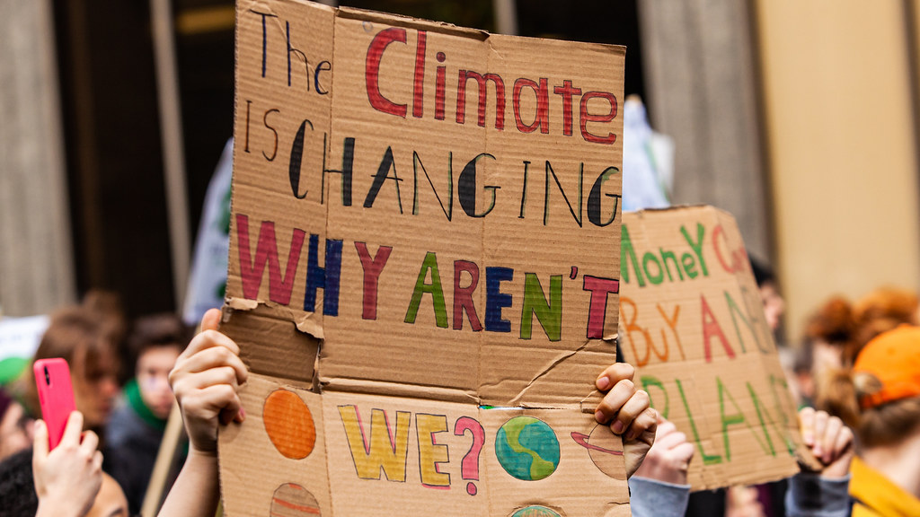 Protester holding up placard 'The climate is changing why aren't we?'