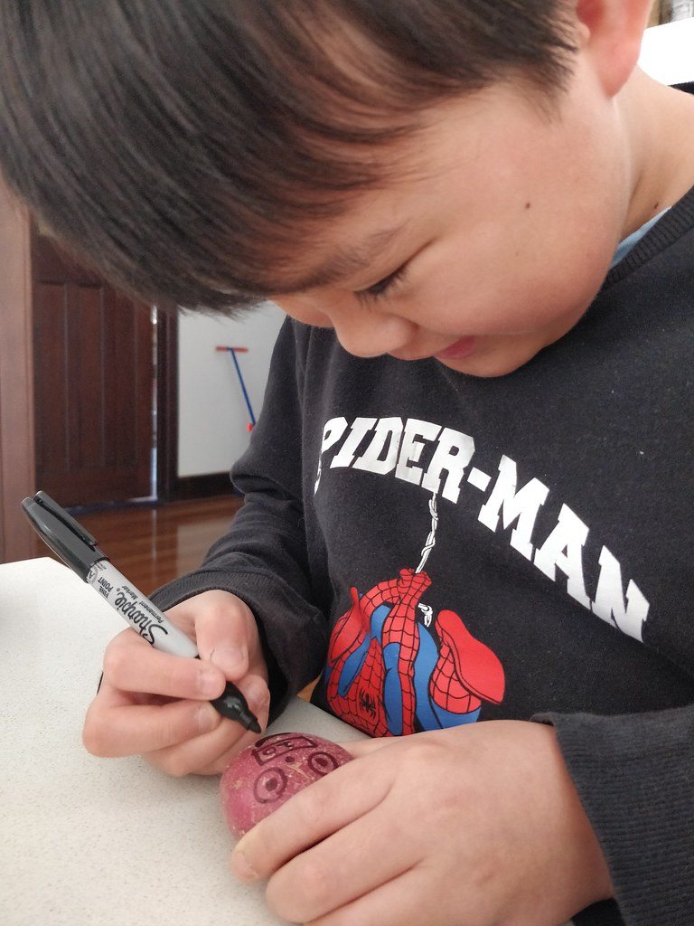 Isaac drawing Rooty on a potato
