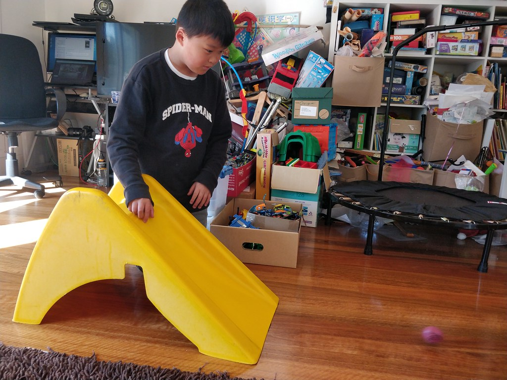 Isaac rolling Rooty down a slide for his Potato Olympics - maths measurements homework