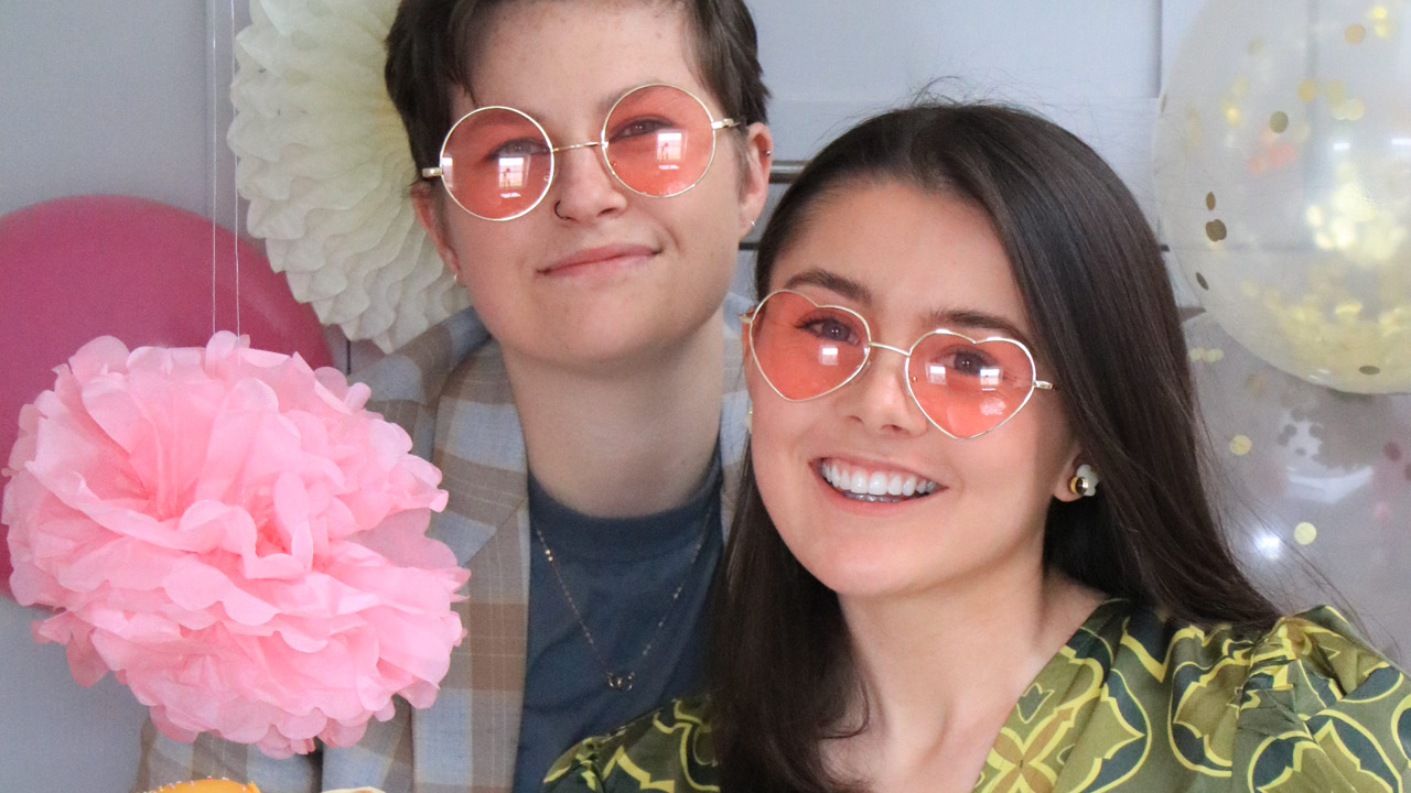 Two people posing in pink sunglasses surrounded by balloons