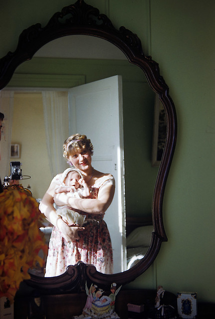 My Mom holding a REALLY young me. Dad took this Kodachrome slide in a mirror and his camera is visible in the background. Milford Connecticut. Jan 1959