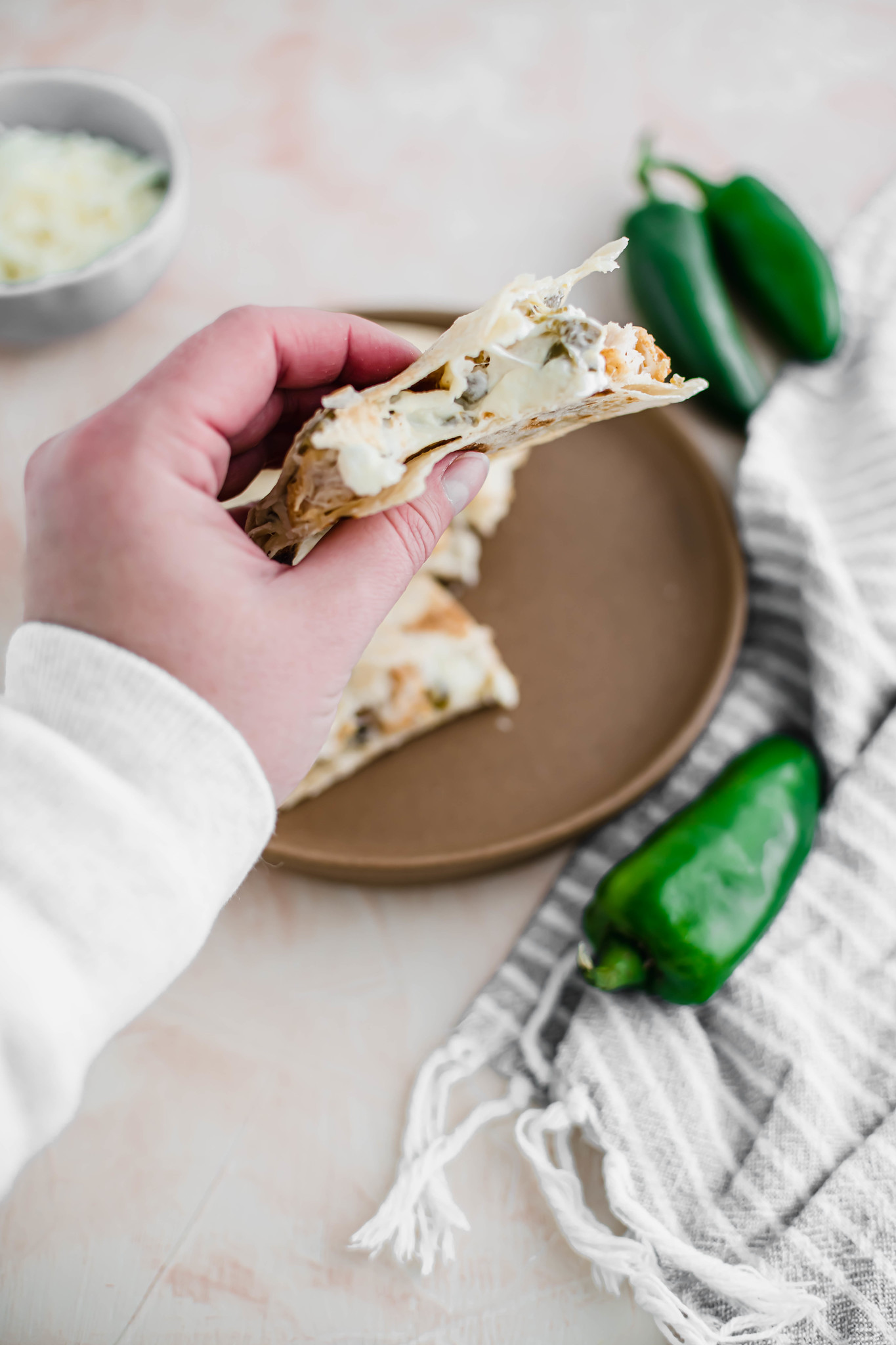 Hand holding jalapeno popper quesadilla with a bite out of it.