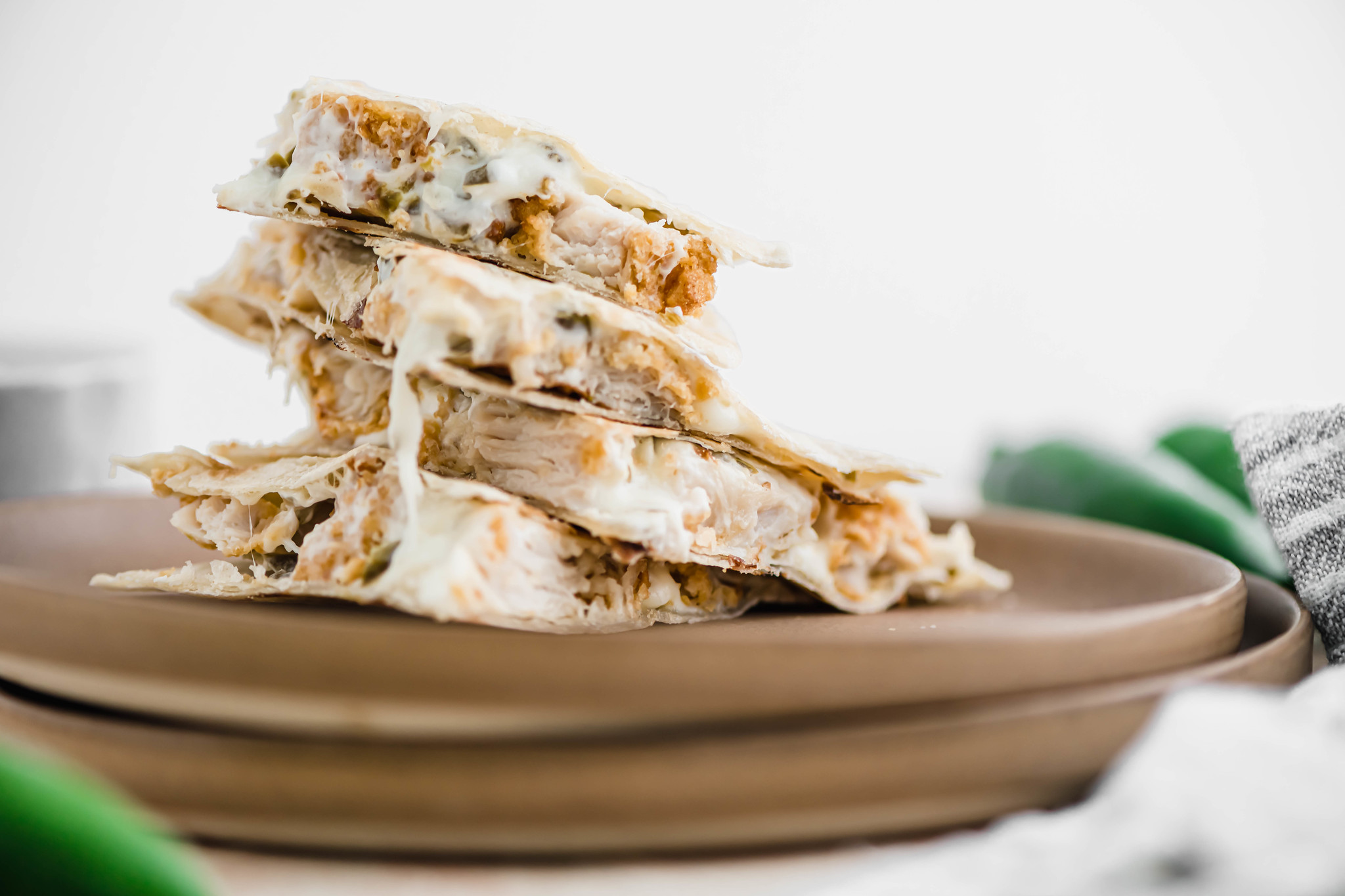 One jalapeno popper quesadilla cut into triangles and stack on top of two clay colored plates.