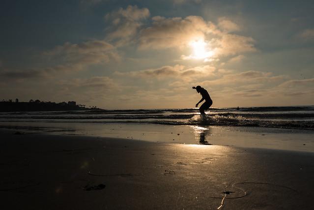 Skimboarding at sunset