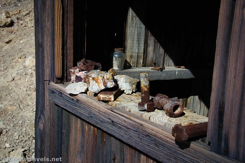 Nuts and bolts and rock in one of the windows of John Cyty's Cabin, Death Valley National Park, Carlifornia
